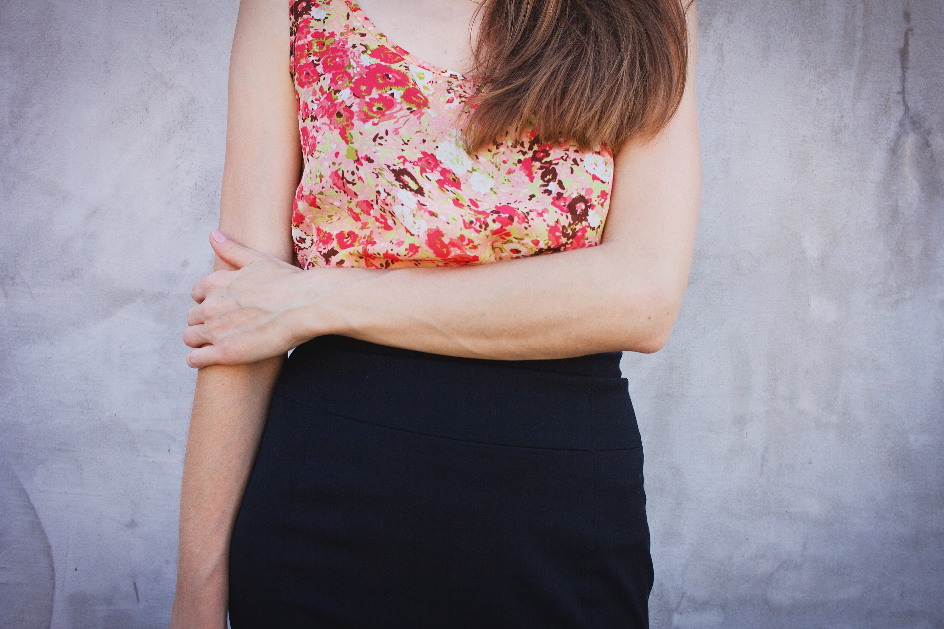 Woman standing with arm across abdomen